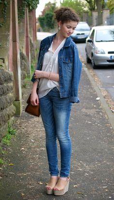 Acheter la tenue sur Lookastic:  https://lookastic.fr/mode-femme/tenues/veste-en-jean-chemisier-boutonne-jean-sandales-compensees-sac-bandouliere/1942  — Sandales compensées en cuir brunes claires  — Jean bleu  — Veste en jean bleue  — Sac bandoulière en cuir brun  — Chemisier boutonné blanc