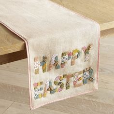 Our jute and polyester table runner showcases a colorful beaded motif with sweet little blossoms and a pleasing pink border.