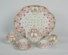 <b>RUSSIAN PORCELAIN TETE A TETE, 19th century;</b> <br /> bearing crowned A mark in red; monogrammed <i>AM</i>; length of tray: 11 in.