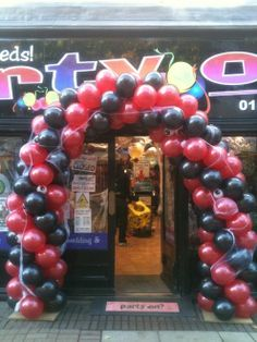 Black and red twisted balloon arch with attached cobweb.