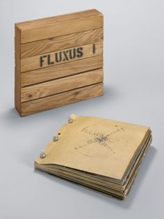 """Fluxus 1,"" 1964-65, Fluxus Edition announced 1962. Book with offset, metal bolts, and stamped ink, containing objects in various mediums, in wood box. Edited and assembled by George Maciunas. 23 1/2 x 22 1/2 x 4 1/2″ (59.7 x 57.2 x 11.4 cm). The Museum of Modern Art, New York; The Gilbert and Lila Silverman Fluxus Collection Gift, 2008."
