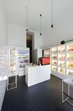 Super Mari' shop and cafe in Vienna by Lukas Galehr where items can be hidden away behind a grid of white ceramic tiles.