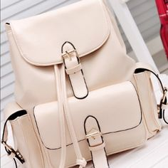 FOLDOVER BUCKLED BACKPACK - BEIGE Pack all your things up in this beige faux leather backpack. The pockets found that the front and sides make this bag very useful in any type of adventure you have in mind. It also has adjustable back straps and snap button/drawstring closure for added style. The interior of this pack is fully lined with an extra zip pocket and smartphone compartment. A perfect match to your school uniform or office wear. Bags Backpacks