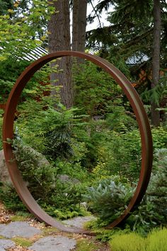 A free-standing large steel hoop acts as a moon gate of sorts partway down the hillside