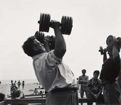 Larry Silver (United States, New York, Bronx, born 1934)  Muscle man with dumbbells, 1954, printed 1985  Photograph, Gelatin-silver print, Image: 11 5/8 x 13 1/2 in. (29.53 x 34.29 cm); Sheet: 15 7/8 x 20 in. (40.32 x 50.8 cm)  Gift of Bruce Silverstein (AC1998.106.8)  Photography Department. LACMA