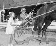 1950-Goshen, NY- Seated in a sulky is the film star James Cagney while little Dolly White, aged 7, holds up her program for Jimmy to autograph. Jimmy rode around the Goshen track in full racing dress in a sulky in the good time of 2:06 3/4 for the mile. After his ride, Jimmy autographed programs for all those who bought war bonds. This was part of a two-day war bond drive at this trotting center. Dolly was the first girl to buy a bond and also the first to get that autograph.