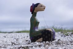 Thai Figurine by William Patrick  This image combines a handmade Thai female figurine, a rough pebble walkway, and a hazy blue sky along a road near my home. Her brightly colored clothes and distinctive facial features catch the eye, and her poise and elegance as she sits watching something out of the frame are engaging.
