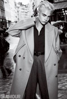 Photographed in black and white, Cara Delevingne poses in Michael Kors Collection coat, blouse, trousers and belt