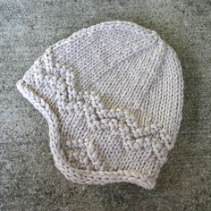 Free pattern for a super-quick, adult-sized earflap hat (made for winter beach hikes). Bully yarn (or two strands held together) knits up fast.