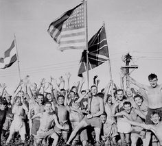 Allied POWs at Aomori Camp in Japan celebrating their liberation by the US Navy. They're waving the flags of the US, Great Britain, and Holland.
