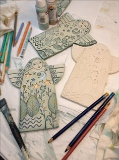 Sue Davis is using acrylic paints and colored pencils to finish her clay angels.