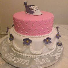 Pink, gray, and white baby shower cake with shoe topper