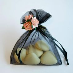 A black organza pouch filled with heart chocolate dragees and finished with pink roses.  From http://www.elenamaria.co.uk