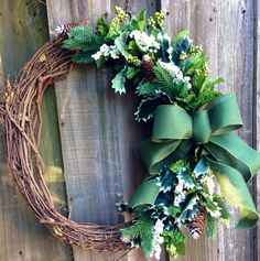 Winter grapevine wreath with evergreen/pine, green and white berries, pinecones, and a simple green bow. on Etsy, $55.00