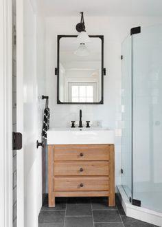 Banheiro pequeno branco com torneira detalhes pretos e gabinete de madeira