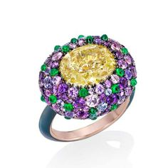 Sotheby's Diamonds - Ricci Ring. Royal Hues of Provence. Centering a fancy yellow oval cut diamond, weighing 5.06 carats. Surrounded by a border of pavé-set amethysts, purple sapphires and emeralds. Mounted in 18k white gold and steel.