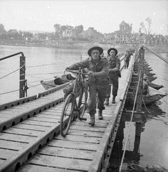 Infantry with bicycles cross the River Seine across a pontoon bridge at Vernon, 27 August 1944.