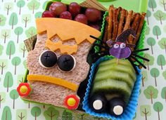 """this Frankenstein-esque feast with a ham and cheese sandwich, complete with cheddar cheese features and olive-mozzarella eyes. His buggy neighboring friend is made with sliced kiwi and olives. Grapes (so like eyeballs!) and pretzel """"bones"""" further balance out this monstrously cool Halloween lunch."""