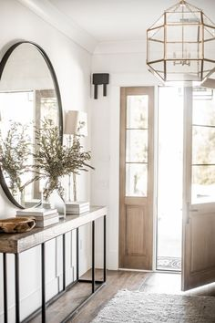 Our entry way already has this modern farmhouse feel to it and we wanted to keep things very simple and clean here! We stacked coffee table books, added in a wood bowl, and completed the look with some fresh olive branches! | Entry Styling | Styled and Photographed by Public 311 Design | #circlemirrorentryway #modernfarmhouseentry #entrywaydecor #entrytabledecorideas #olivebrancharrangement #olivebranchentrydecor