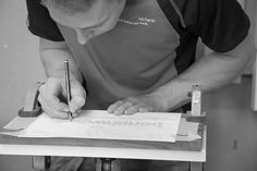 Wood carving at Benchwood Kitchens workshop - transferring the lettering to the work piece before you can begin to carve out the lettering. www.benchwoodkitchens.co.uk