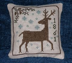 Cross stitch small winter pillow with deer and snowflakes.  Design by Tina Woltman.  I altered the design a little bit.