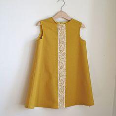 Toddler Girls sleeveless dress is made from a golden mustard cotton linen blend. The dress has a cream lace detail down the front, with butterflies