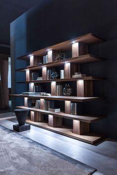 """David Chipperfields hat sein """"Bookshelf"""" für Riva1920 überarbeitet. Die 2019-Variante erinnert einerseits an die schweren Massivholz-Vorgänger aus der Möbelgeschichte, andererseits spricht die Struktur eine nach wie vor moderne Sprache. Die vertikalen Streben (es sind eher Blöcke) sind abwechselnd seitlich versetzt, sodass ein aufgelockertes Bild entsteht. Außerdem ist der dritte der ohnedies breiten Einlegeböden (von unten) tiefer und bietet sich sogar als Schreibtisch an. © Riva1920 Singapore House, Bookshelves, Bookcase, Dining Area Design, Wine Cabinets, Wine Storage, Architecture, Modern Contemporary, Furniture Design"""