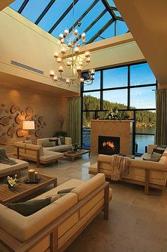 "Dramatic lake-scape frames a marble fireplace. Expansive floor-to-ceiling window panes blend seamlessly to create a ""wow"" skylight."