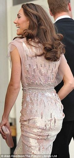 Kate Middleton. Photo. In a shimmering figure-hugging palest pink Jenny Packham gown, accessorised with nude LK Bennett heels shoes and a toning clutch bag