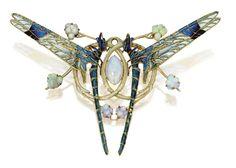 Un bello broche-colgante realizado por Lalique hacia 1903-1904 montado en oro con esmalte y ópalos. Lo más llamativo es la manera en que se enfrentan las alas de las libélulas con un esmalte pliqué-à-jour tan delicado y transparente que casi parece cristal de colores.