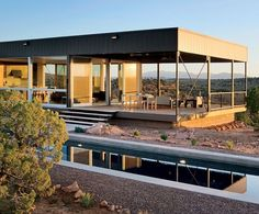 Soon after attending an open-house reception for Marmol Radziner Prefab's prototype, a Colorado couple commissioned the firm to create a custom prefab residence for vacation use. Above: With their sliding glass doors transitioning to covered decks, the dining and living areas, which feature furniture by Marmol Radziner, extend effortlessly into nature. Structural panels in the floor and ceiling provide superior insulation. (October 2008)