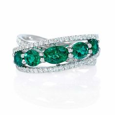 This stylish 18k white gold ring features 74 round brilliant cut white diamonds of F color, VS2 clarity and of excellent cut and brilliance, weighing .48 carat total with 5 oval cut emeralds of exquisite color, weighing 1.51 carats total.
