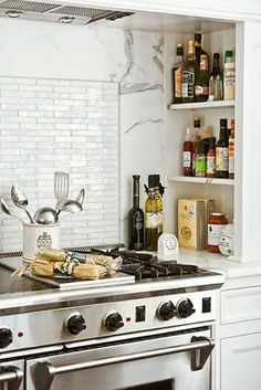 Amazing Kitchen Range Nook With Built In Marble Shelves Filled With Spices,  White Marble Slab Countertop And Iridescent Tile Cooktop Backsplash.