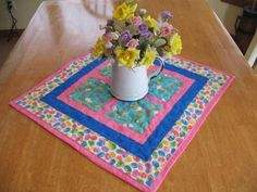 A Quilted Table Topper/Runner is like a paned window full of Easter Bunnies looking for those colored eggs. The center blocks are white bunnies with a soft teal blue background. The center blocks are encased with pink and another row of blue cotton fabric. The outer sashing is a lot of colorful easter eggs. The fabrics are 100 percent cotton. The batting is Pellons Nature Touch Cotton. It measures approximately 21 inches square. It is machine washable and dryable on a low heat setting....