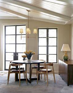 木製の丸いテーブルとチェア。天井からはカジュアルな照明がつり下げられています。