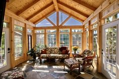 Sunroom, Just constructed over open exterior decking. Pine post and beam structure with heated slate floor with views of lake. Exterior sitting area on both sides of sunroom. Exterior of sunroom is board & batten to blend in with waterfront setting., New sunroom in the Kawartha Lakes       , Porches Design