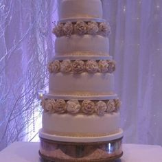 Four tier wedding cake with collars of hand made sugar roses.