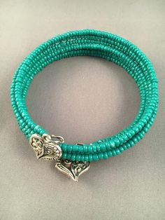 This memory wire bracelet is made of rich green mini seed beads with a filigree heart charm