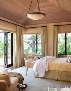 Designer Suzanne Tucker created this country house in California. A ceiling of natural cedar brings the outdoors in and creates texture and warmth in the master bedroom. The silk and linen Stark rug adds plush softness. Curtains and bed skirt are Leopard by Raoul Textiles. Dome pendant light from Hilliard.   - HarpersBAZAAR.com