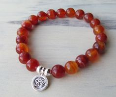 This bracelet is composed of quality 8mm (medium) Red Banded Agate beads and a fine silver Thai OM charm. The charm is surrounded by two matching silver beads.    Agates are wonderful protection stones ~ cleansing and protecting your aura. This is also a stone to combat stress and foster strength within the wearer. Agate is also known as a powerful emotional healer. Associated with the Solar Plexus Chakra..