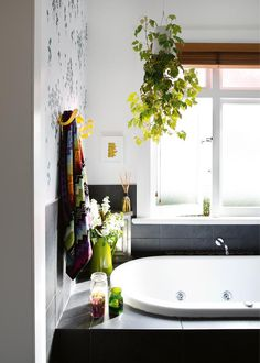 An upside-down hanging planter works beautifully to soften the lines in this bathroom and creates a mini jungle effect. Via Inside Out/Desire to Inspire.