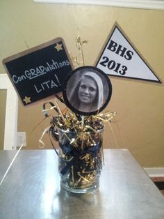 Centerpiece for graduation party. Chalkboard made using chalkboard paper I bought at Michaels craft store. Attach long ribbons with  black and gold balloons to the center.