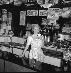 """In this photo darling soda-jerk Margie Chrisman poses while sipping a fountain Coke and waiting for the after-school crush. See the """"signs of the time"""" posted behind her! 1950, Rexall drugstore, on a corner in Grand Rapids, Michigan."""