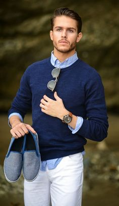Shop this look on Lookastic:  http://lookastic.com/men/looks/crew-neck-sweater-long-sleeve-shirt-jeans-slip-on-sneakers-sunglasses-watch/11345  — Light Blue Chambray Long Sleeve Shirt  — Dark Brown Sunglasses  — Brown Leather Watch  — Navy Crew-neck Sweater  — Grey Canvas Slip-on Sneakers  — White Jeans