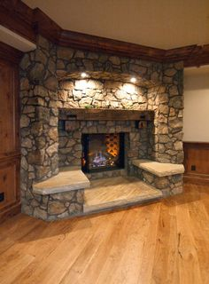 rustic fireplace with lights on the mantle with stone seating on the sides