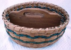 "This handwoven basket comes with a wooden base with a wooden handle making this a divided basket.Teal reed has been woven into the sides. Wonderful to use for parties, camping, cookout, or just carry items around. Size 12"" across the top x 5 1/2"" tall top of handle."