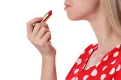 woman applying red lipstick isolated on white background makeup and