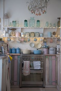 Inspirational pastel kitchen in the home of Tamsyn Morgans, hand made doors from pallets, perfect arrangement for a small and individual kitchen. pink, pale blue, mint, blue glass kilner jars, enamel vintage kitchenalia.
