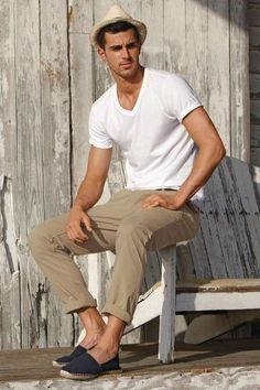 Pair a white v-neck tee with camel chinos for a refined yet off-duty ensemble. Finish off this look with navy canvas espadrilles. Shop this look on Lookastic: https://lookastic.com/men/looks/v-neck-t-shirt-chinos-espadrilles-hat-belt/10414 — Beige Straw Hat — White V-neck T-shirt — Brown Leather Belt — Khaki Chinos — Navy Canvas Espadrilles