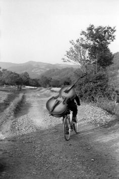 A bass player riding his bike to play at a village festival near Rudnick, Yugoslavia 1965. Photographed by Henri Cartier-Bresson.